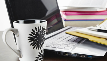 Coffe cup and day planner with pen and laptop